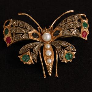 Spilla a farfalla in oro, perle e pietre preziose .